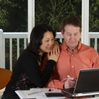 couple looking at a laptop while smiling