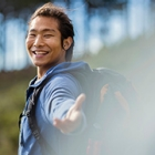 Happy young asian man smiling and looking at camera